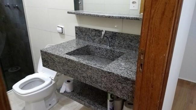 banheiro com bancada e cuba esculpida em granito cinza ocre