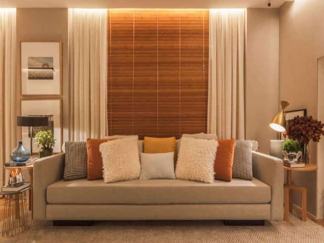 Sala com persiana de madeira e cortinas brancas