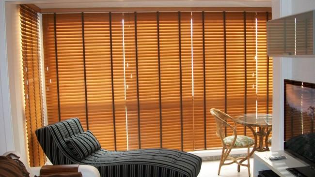 Sala com persiana de madeira que contribue para o isolamento térmico e acústico
