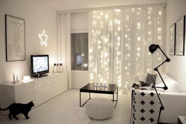 sala branca com cortina de tecido com luzinhas