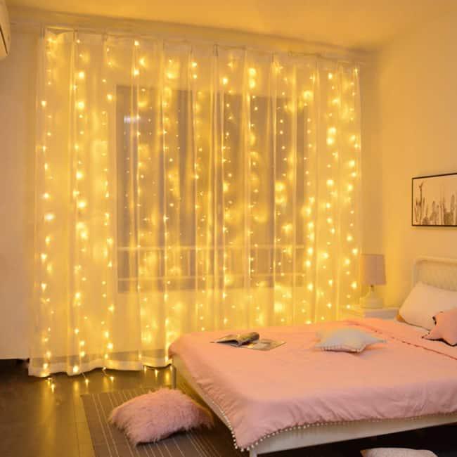 quarto com cortina branca e cortina de luzinhas