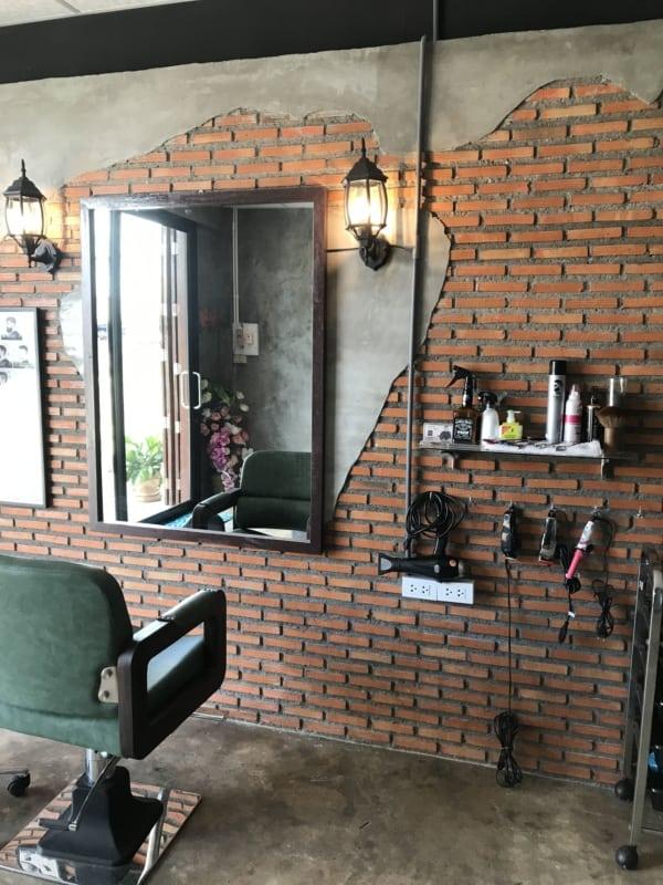 decoração para barbearia com parede de tijolos aparentes