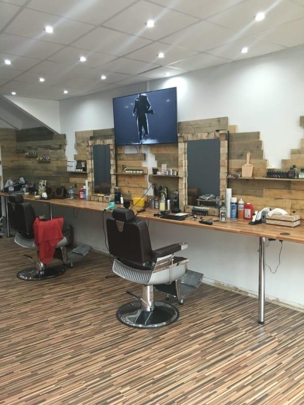 barbearia com parede decorada com revestimento de madeiras