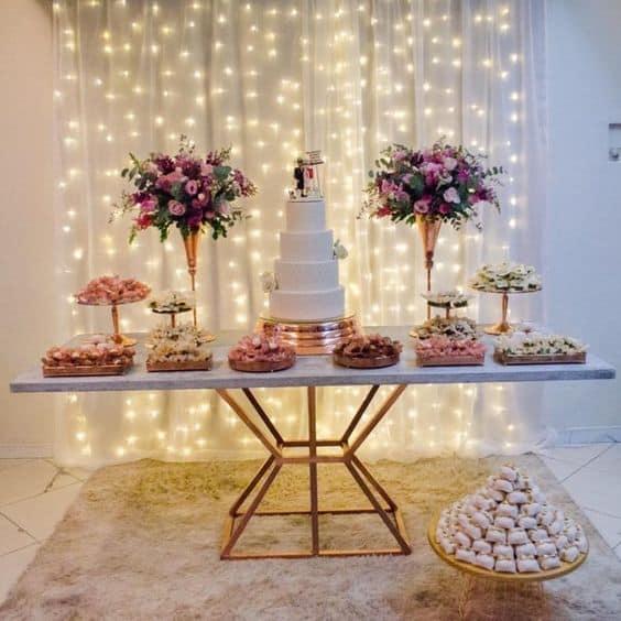 decoração de festa com cortina de led com tecido atrás da mesa do bolo
