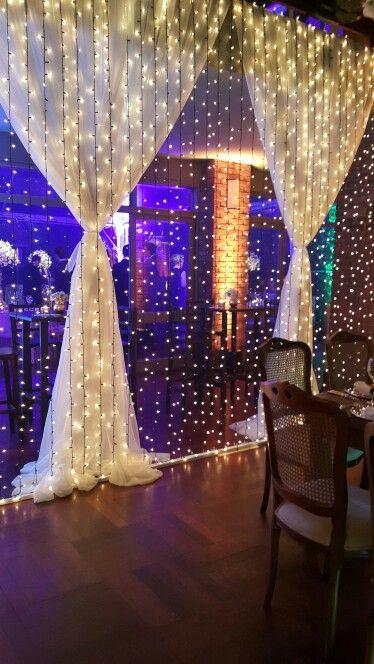 decoração de festa com cortina de luzinhas e cortina de tecido