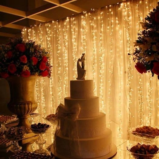 bolo de casamento com painel de fundo de luzinhas