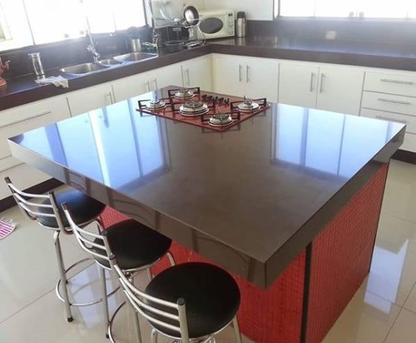 cozinha com ilha de granito marrom absoluto e fogão cooktop