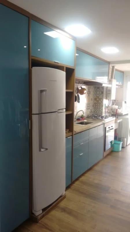 cozinha com armários em compensado naval e acabamento em vidro azul