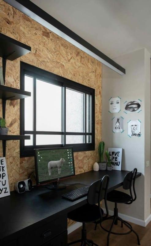 home office com parede revestida de OSB