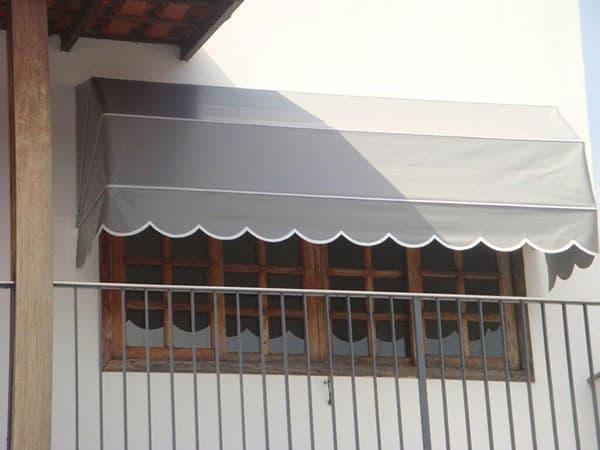 janela de madeira com toldo capota cinza