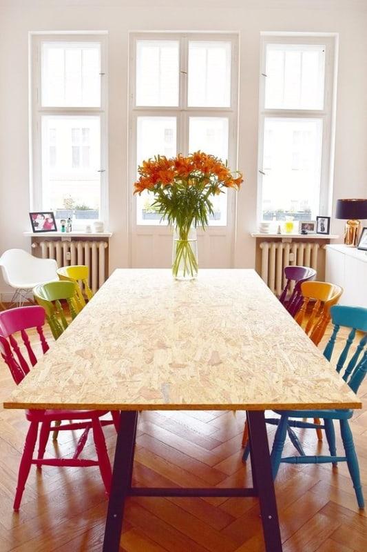 mesa moderna em OSB com cadeiras coloridas