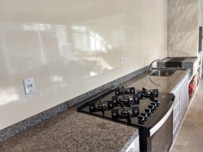 cozinha com bancada de granito cinza ocre e fogao embutido