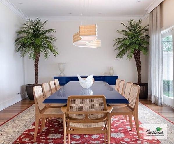 sala de jantar decorada com vasos de palmeira fenix