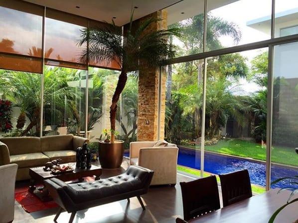 sala com pe direito duplo e vaso de palmeira fenix
