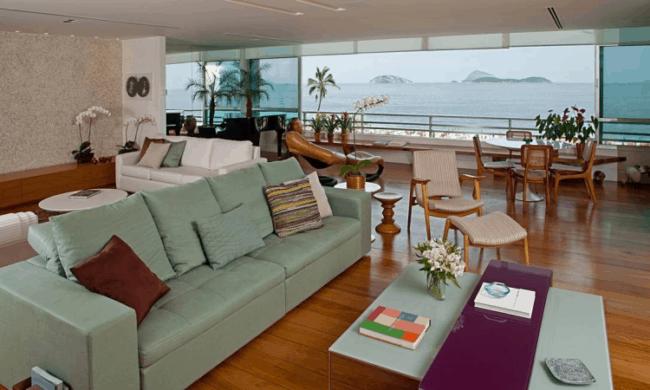 sala grande com piso de madeira e sofa verde menta