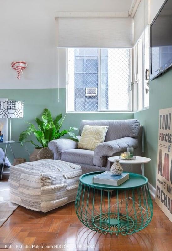 sala com meia parede verde menta e poltrona cinza