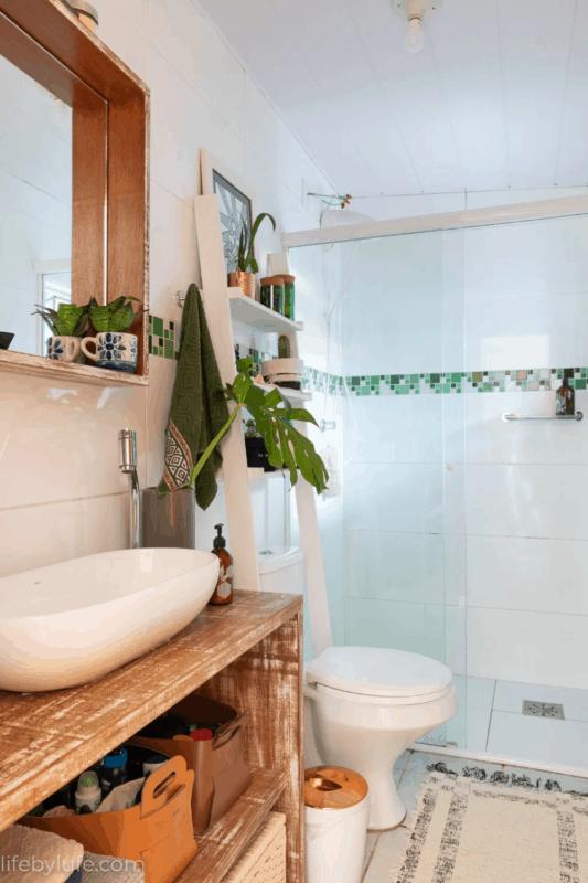 banheiro com escada decorativa branca sobre o vaso