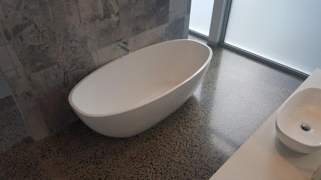 piso de concreto polido em banheiro com banheira