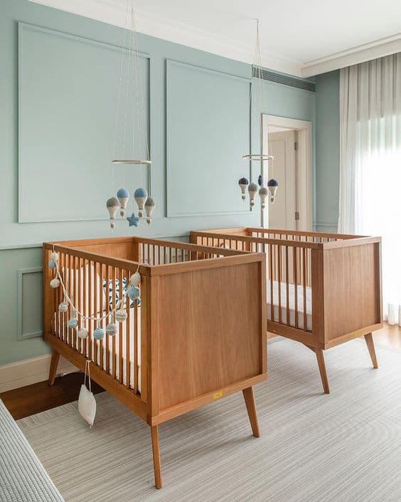 quarto de bebe com parede verde menta e berco de madeira