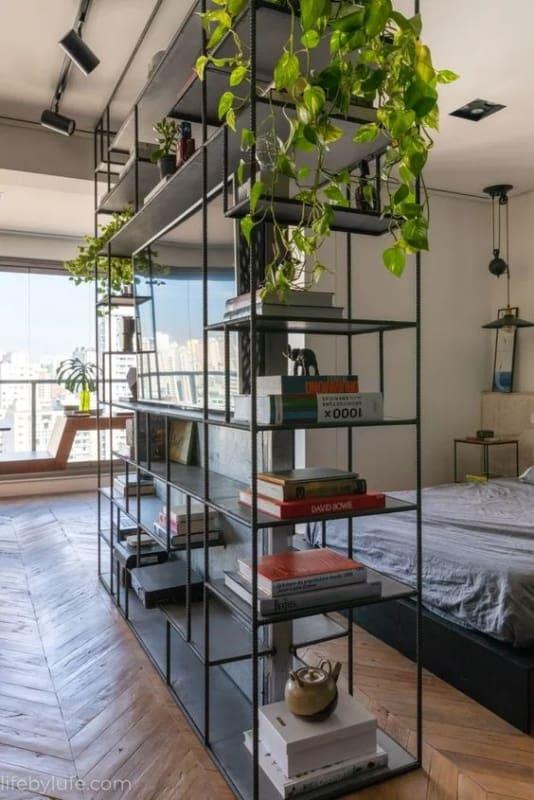 estante industrial preta no quarto com livros e plantas