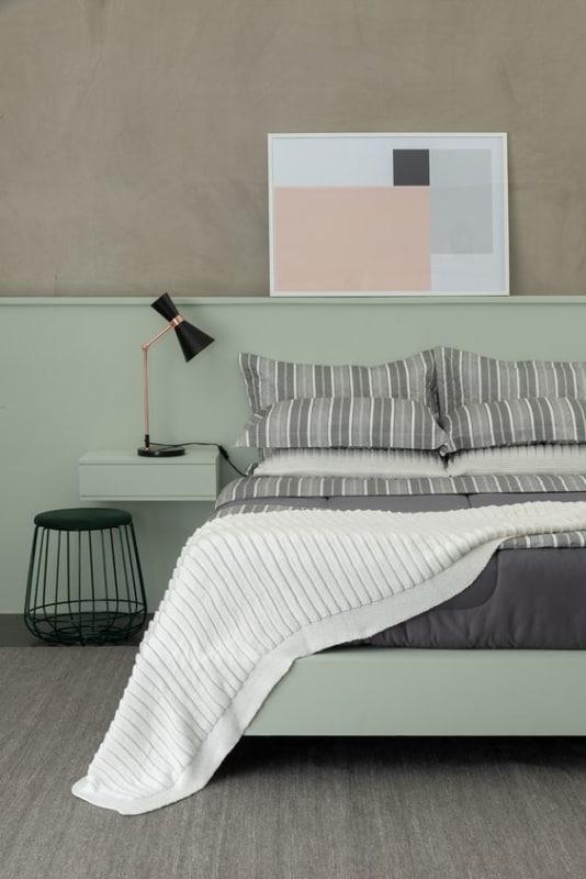 quarto moderno com parede cimento queimado e painel verde menta