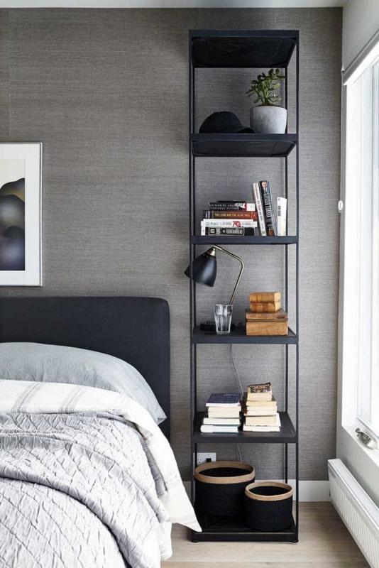 quarto com estante industrial preta ao lado da cama