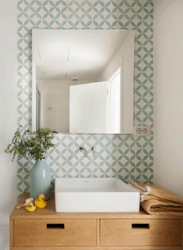 banheiro com revestimento geometrico em verde menta e branco