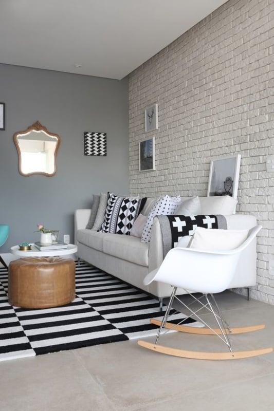 sala com parede cinza decorada com quadros e espelho