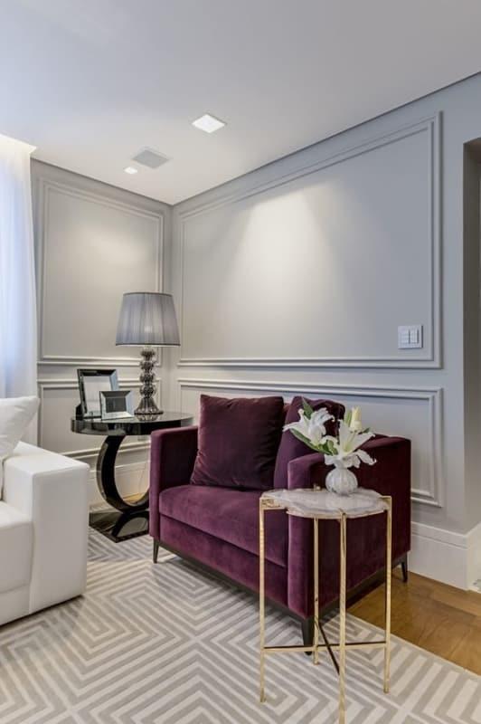 sala com parede cinza claro e poltrona roxa