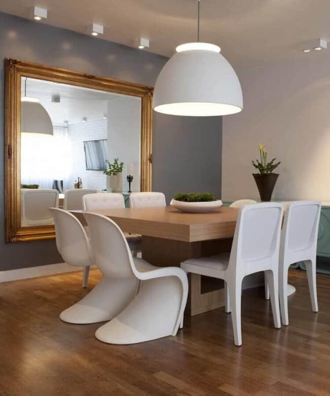 sala de jantar com parede cinza e espelho grande
