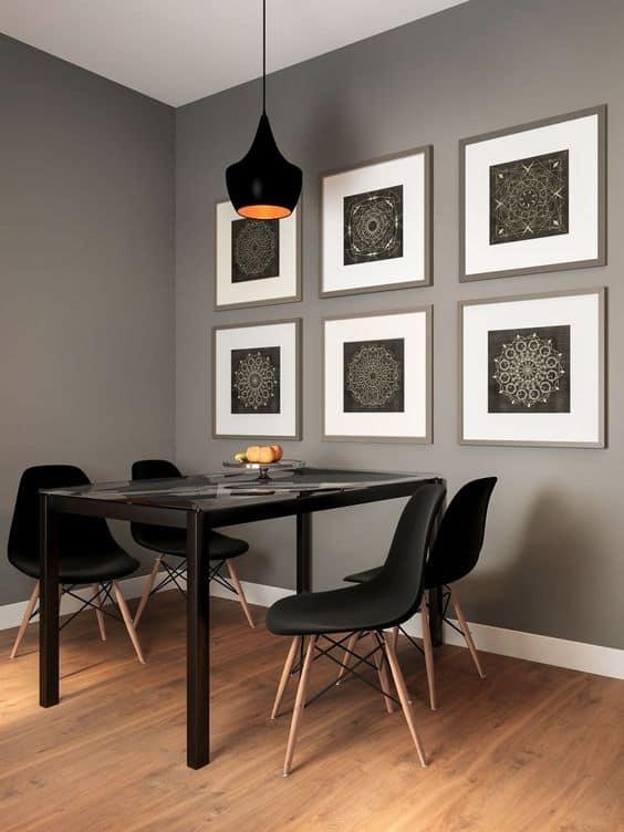 sala de jantar com parede cinza e decorada com quadros