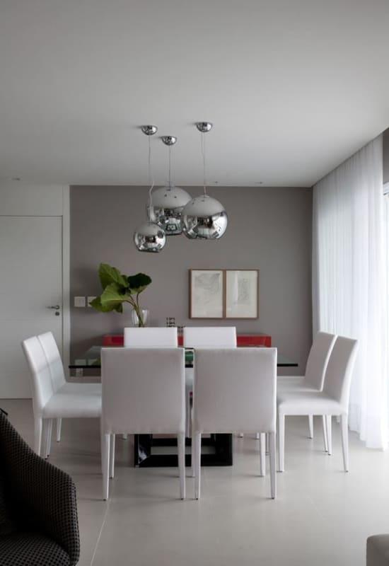 sala de jantar moderna com parede cinza e cadeiras brancas