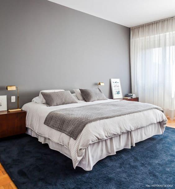 quarto com parede cinza e tapete azul marinho