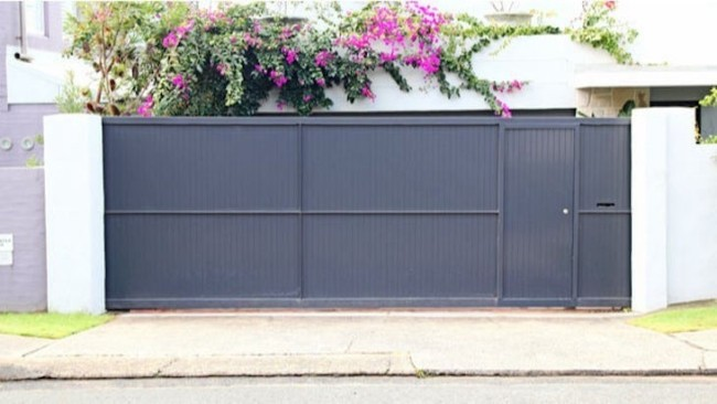 fachada de casa com portao de correr fechado e entrada social