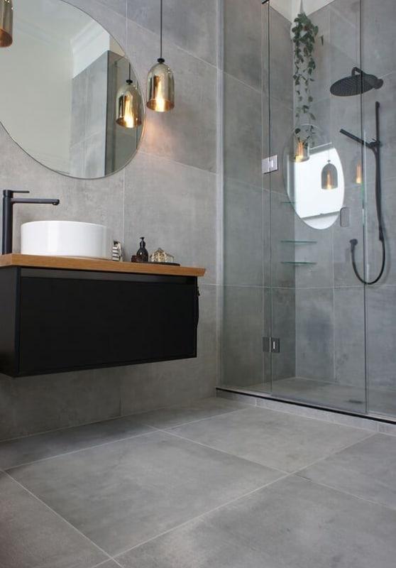 banheiro com piso e revestimento cimento queimado