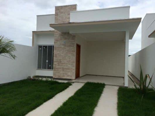 casa pequena com telhado embutido e garagem na frente