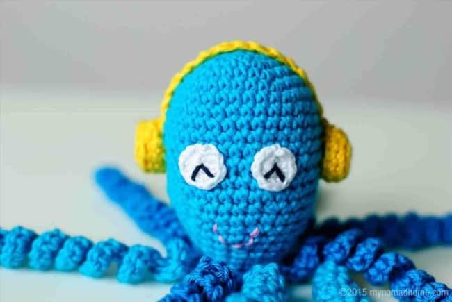 polvo de croche azul com fones de ouvido