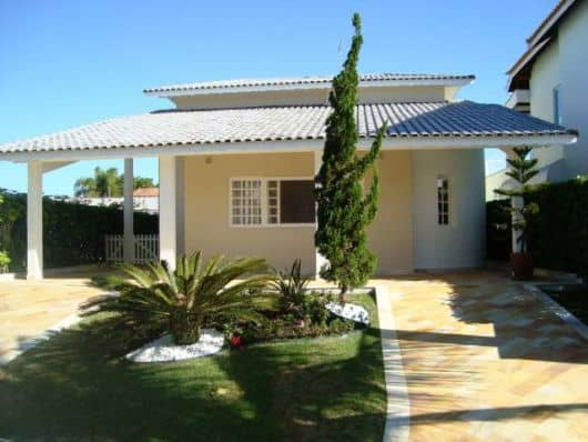 fachada de casa terrea pequena com garagem e telhado aparente