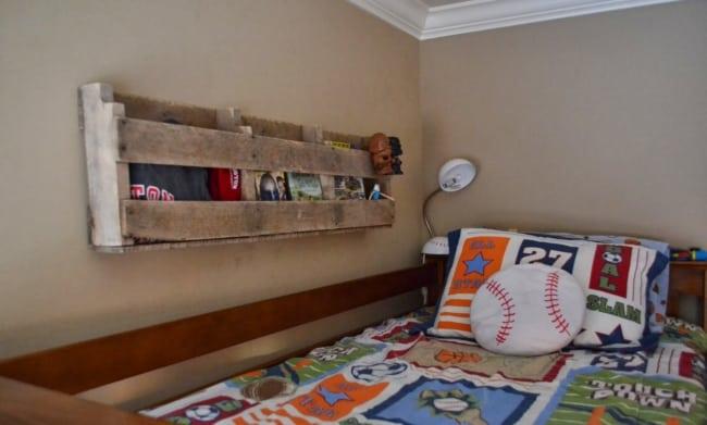 quarto com prateleira de pallet ao lado da cama