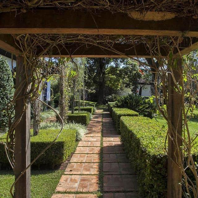 O caminho no jardim passa pelo pergolado e cria um projeto incrivel