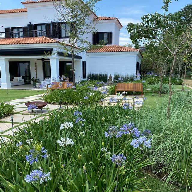 O patio possui uma entrada bem alinhada com o gramado e os canteiros