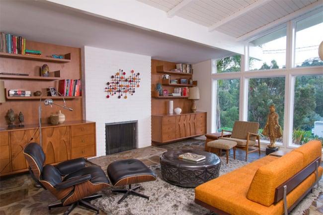 sala com lareira e poltrona Charles Eames com puff