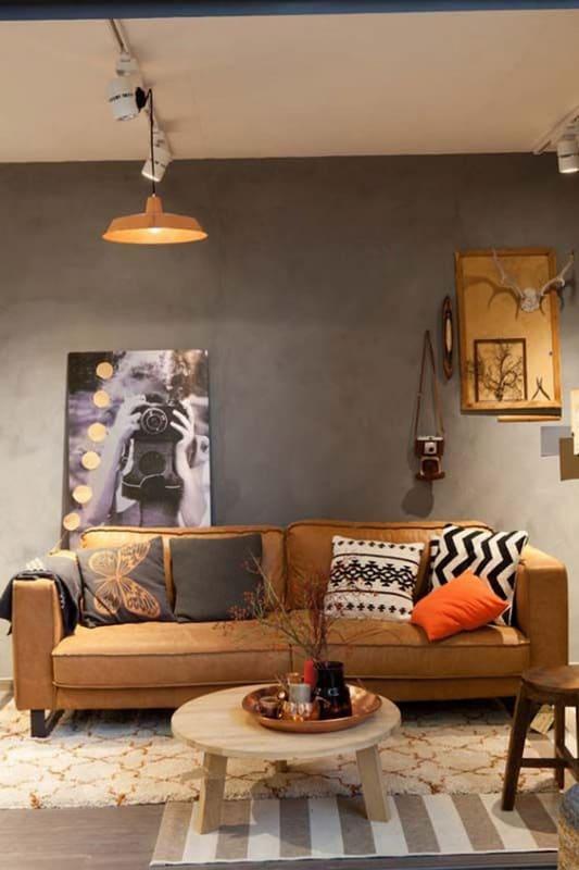 sala com parede de cimento queimado e sofa caramelo