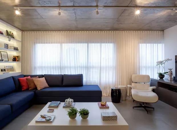 sala com sofa azul e poltrona Charles Eames branca