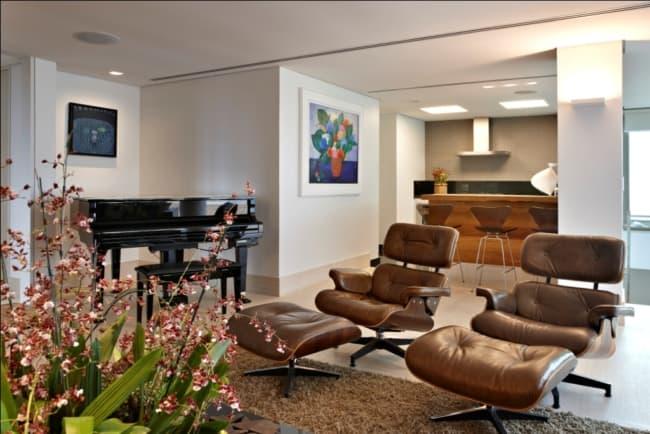 sala com poltrona Charles Eames marrom com puff