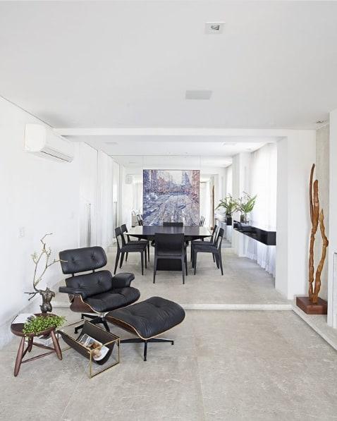 sala com cantinho de leitura e poltrona Charles Eames com puff