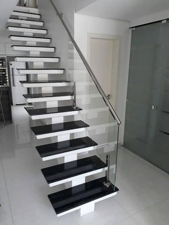 escada espinha de peixe em concreto com guarda corpo de vidro