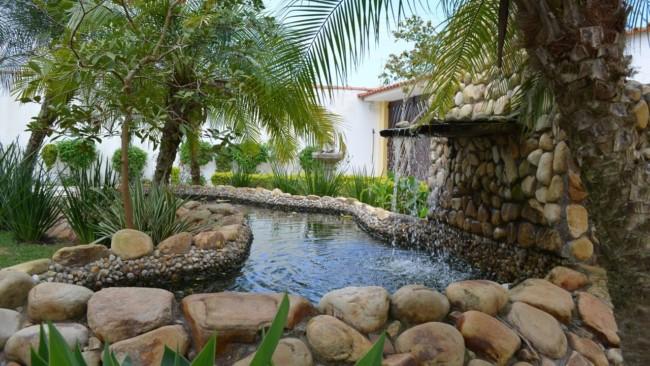 jardim externo com cascata e lago artificial