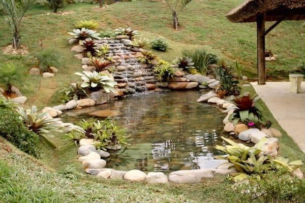 jardim com lago ornamental e cascata de pedras