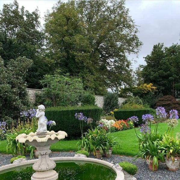 jardim com fonte e vasos de agapanto